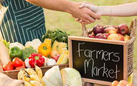 granjero: Farmer sacudiendo sus clientes la mano en un día soleado