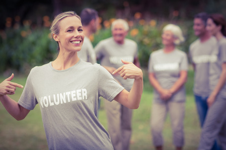 volunteer: Happy volunteer showing her t-shirt to camera on a sunny day