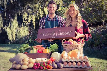 pareja saludable: Agricultores felices de pie en su puesto en un día soleado