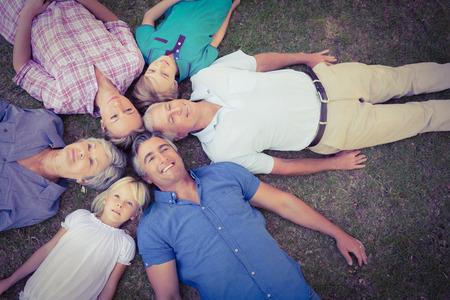 Familia feliz que mira la cámara en un día soleado
