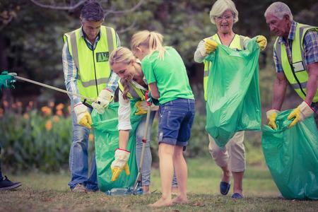 medio ambiente: Familia feliz recogida de basura en un d�a soleado