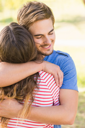handsome man: Cute couple hugging in the park on a sunny day Stock Photo