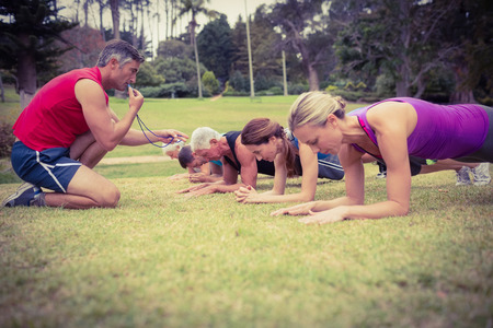 fitness trainer: Happy athletic group training on a sunny day