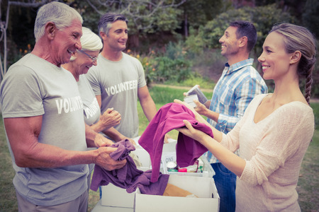 donations: Happy volunteer family separating donations stuffs on a sunny day Stock Photo