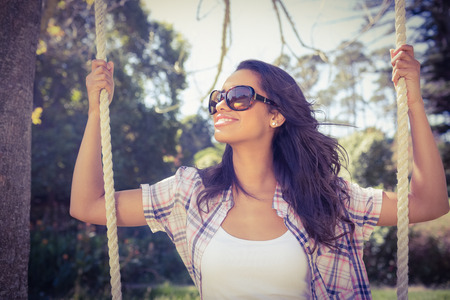 Pretty brunette swinging in park on a sunny day Stock Photo