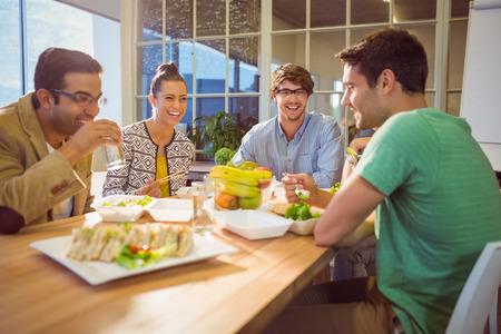 hombre comiendo: Los empresarios jóvenes que almuerzan juntos Foto de archivo