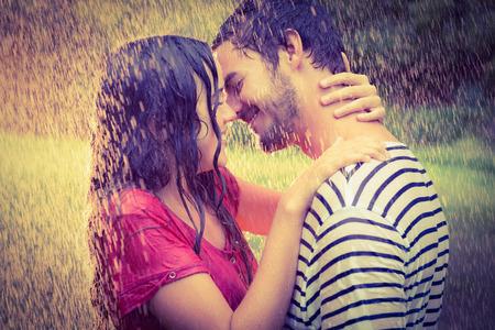 novios besandose: Linda pareja abrazarse bajo la lluvia en el parque