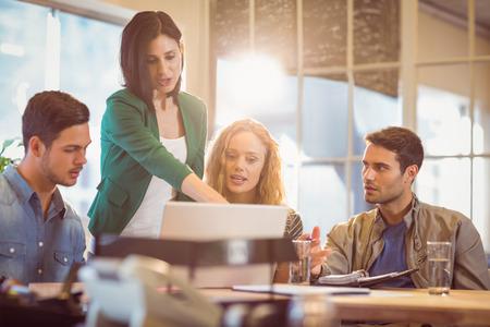 profesionistas: Grupo de jóvenes colegas usando la computadora portátil en la oficina