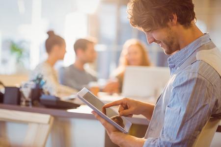 oficina: Hombre joven sonriente que usa la tableta digital en la oficina