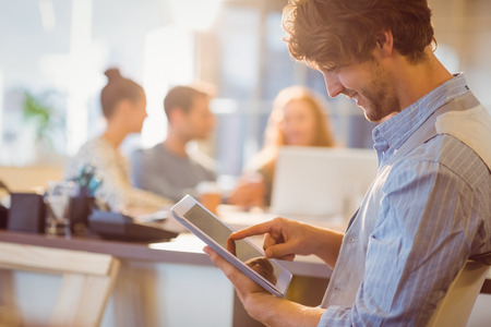 Lachende jonge man met behulp van digitale tablet in het kantoor