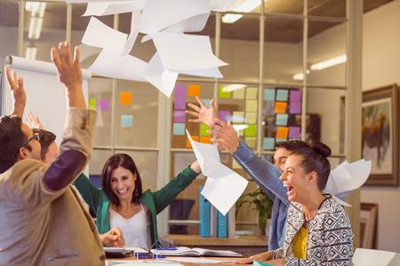 Gruppe Gesch�ftsleute, die feiert, indem er ihren Gesch�ftspapieren in der Luft Lizenzfreie Bilder
