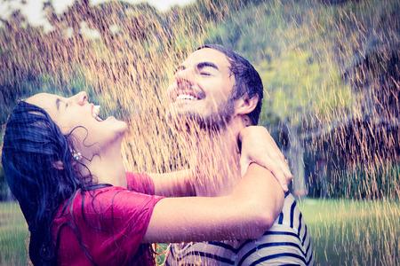 uomo sotto la pioggia: Bella coppia avvolgente sotto la pioggia nel parco
