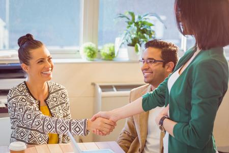 カジュアルなビジネス人々 のデスク、オフィスで笑顔で手を振って