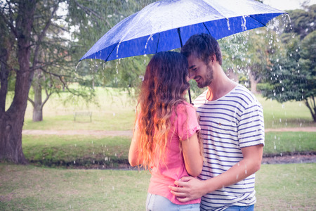 uomo sotto la pioggia: Bella coppia che abbraccia sotto l'ombrello nel parco
