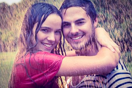 sotto la pioggia: Bella coppia avvolgente sotto la pioggia nel parco