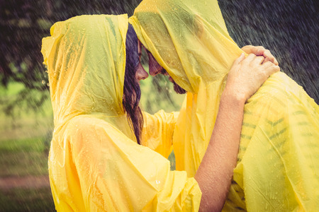 Cute couple wearing protection cape and hugging under the rain in the park Stock Photo
