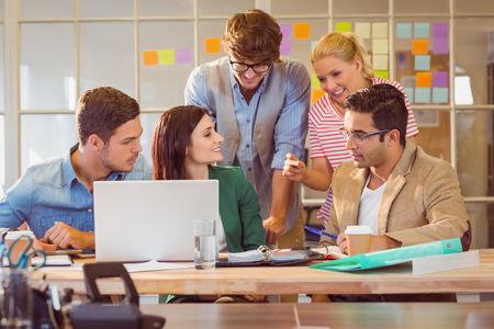 オフィスでの会合でラップトップを使用して幸せな創造的なビジネス チーム 写真素材