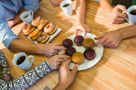multiracial group: Business people taking cakes on table after lunch in the office