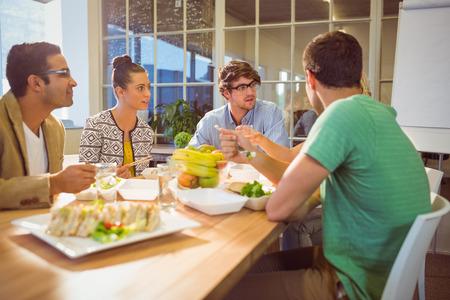 comiendo platano: Los empresarios jóvenes que almuerzan juntos Foto de archivo
