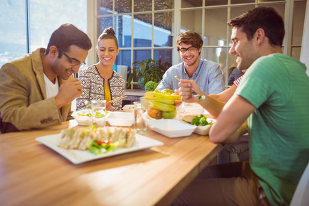 woman eating fruit: Young business people having lunch together