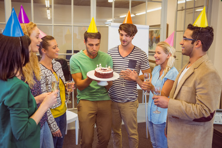 office staff: Businessman blowing candles on her birthday cake in the office Stock Photo