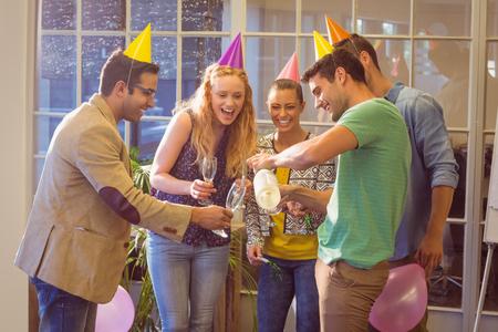 personas festejando: Hombres de negocios creativos que celebran un cumpleaños