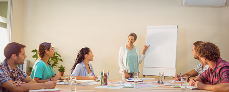 indian style sitting: Casual young businesswoman giving a presentation to her colleagues