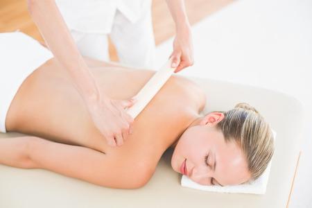 depilacion con cera: Mediados de sección de la mujer terapeuta depilación de espalda en el spa