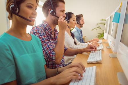 헤드셋을 착용하는 콜 센터에서 함께 작동하는 비즈니스 팀
