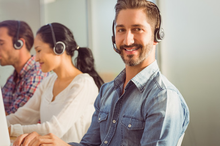 call center woman: Portrait of a smiling businessman working with colleagues in a call centre