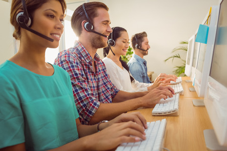 headset computer: Business team working together at a call centre wearing headsets Stock Photo