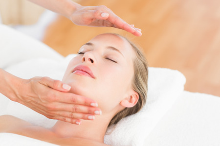 alternative healing: Calm woman receiving reiki treatment in the health spa Stock Photo