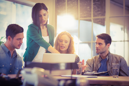reunion de trabajo: Grupo de j�venes colegas usando la computadora port�til en la oficina