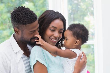 bebe sentado: Padres felices con el beb� en el hogar en la sala de estar