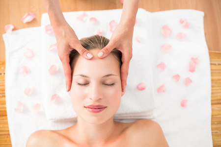 closes eyes: pretty blonde receiving head massage at the spa