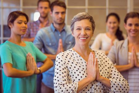 orando: Retrato de una empresaria creativa rezando con su equipo de trabajo
