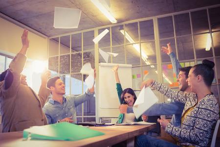 oficina: Grupo de hombres de negocios que celebran lanzando sus papeles de negocios en el aire