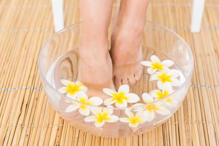 pies: mujer lavando sus pies en un recipiente con la flor en el instituto de spa Foto de archivo