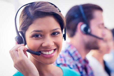 Close up plan of a smiling businesswoman in a call centre
