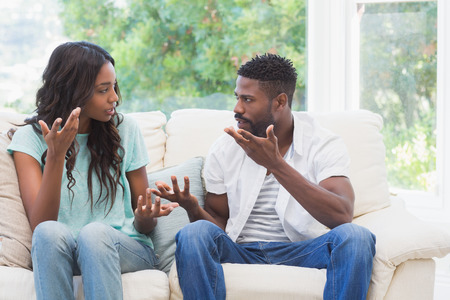 sad couple: Couple having argument on the couch at home in the living room