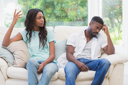Pares que têm o argumento no sofá em casa na sala de estar Imagens