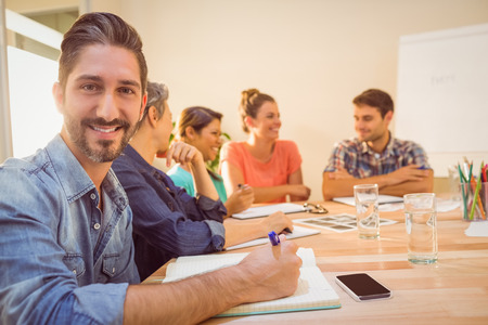 person writing: Casual businessman smiling at camera during meeting in the office