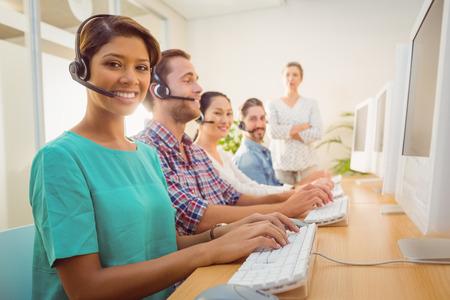 call center agent: Ritratto di agente piuttosto call center che lavora sotto la supervisione gestore