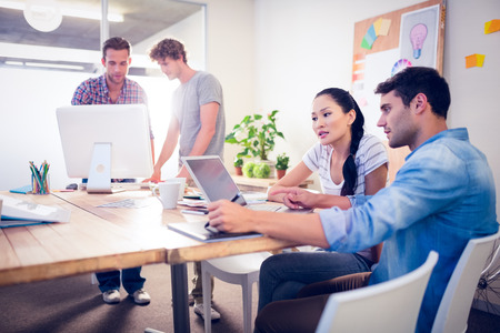 Creative business team gathered around laptops in the office Stock Photo