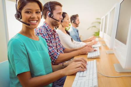 computer center: Retrato de una mujer de negocios sonriente trabajando con colegas en un call center