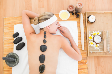 massieren: Schöne Blondine genießt eine Hot-Stone-Massage im Wellnessbereich