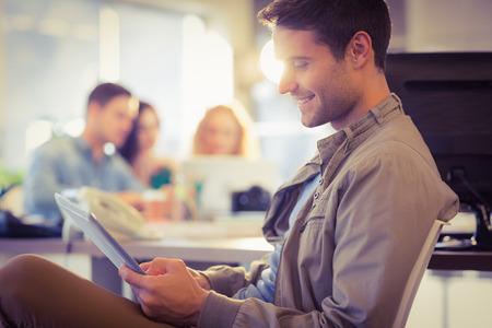 relaxamento: Homem de sorriso novo que usa a tabuleta digital no escritório Imagens
