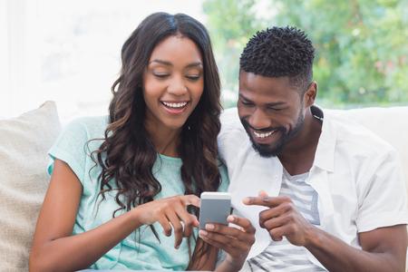 Gl�ckliches Paar auf der Couch mit Telefon zu Hause im Wohnzimmer