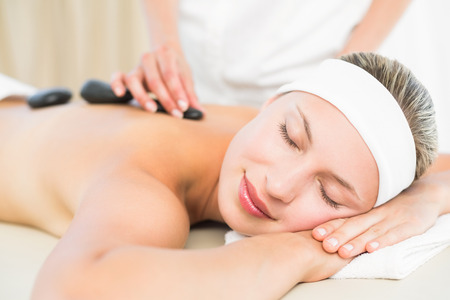massage: Schöne Blondine genießt eine Hot-Stone-Massage im Wellnessbereich