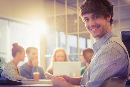 Portrét usmívající se mladý podnikatel s kolegy v kanceláři